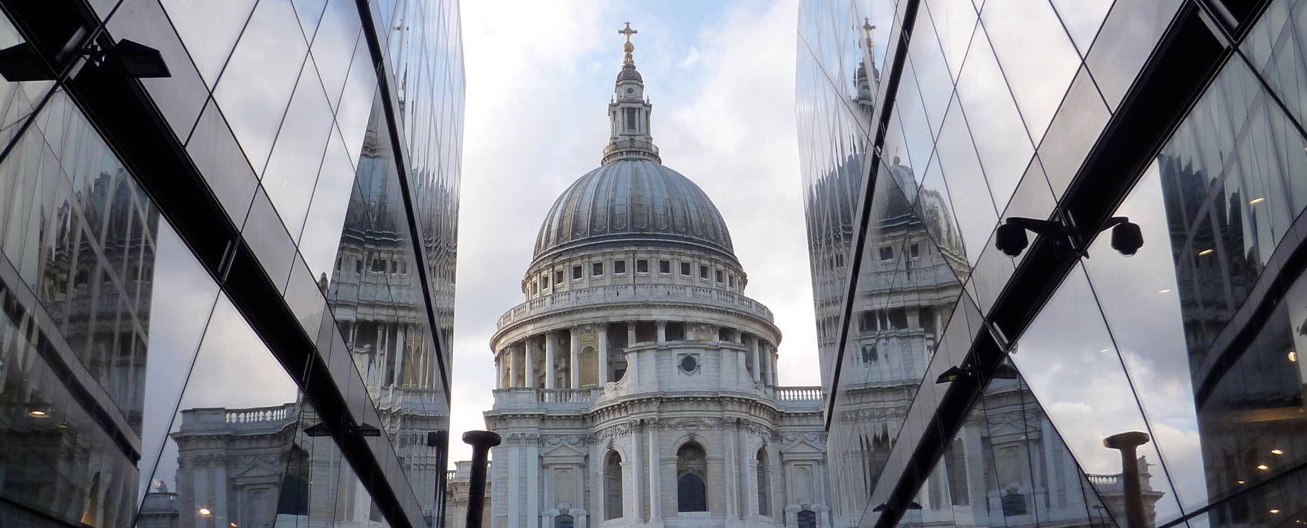 View of St Paul Cathedrail framed by modern glass fronted buildings.